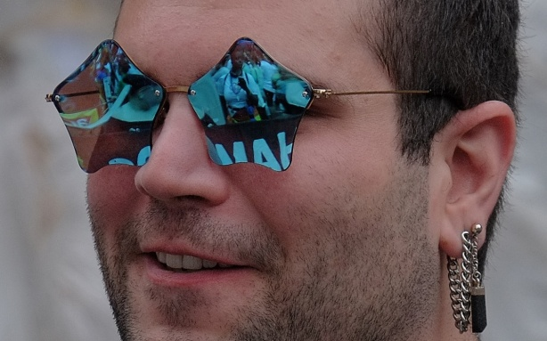 up close shot of man wearing blue star shaped sun glasses