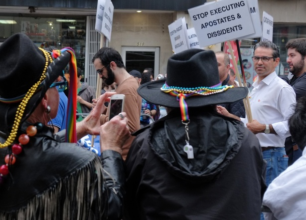 people in black hats and black coats taking photos of group in pride parade marching with signs that say stop executing apostates and dissidents