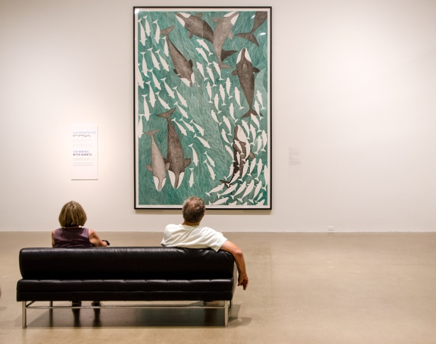 two people sitting on a black sofa, looking at a large painting by Tim Pitsiulak called Swimming with Giants, lots of fish and whales swimming in the water