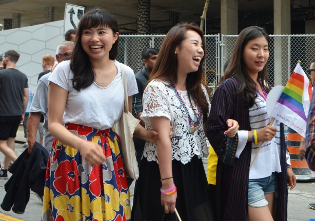 three Asian woman laughing as they walk down the street, looking at something that has made them laugh