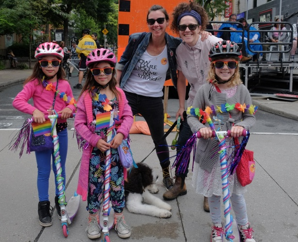 watching the dyke march 2018 on Yonge street, two women with a dog on a leash and three girls on decorated scotters wearing bike helmets and bright sunglasses