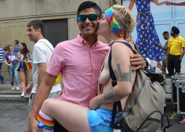 an south asian man in pink shirt and sunglasses gets a topless woman to pose with him, she is kissing him