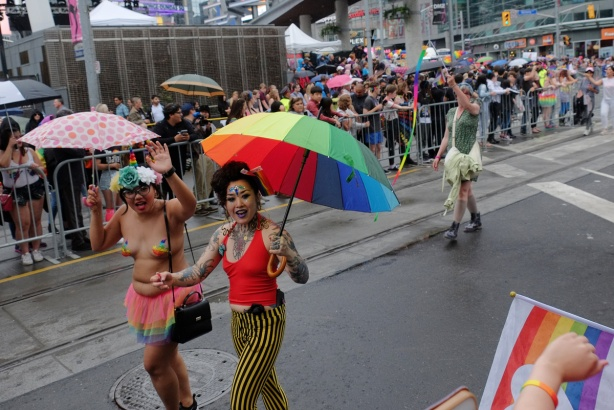 two women walking in the pride parade, crowds on both sides of the street, one is topless with a rainbow frilly skirt and the other has a rainbow umbrella