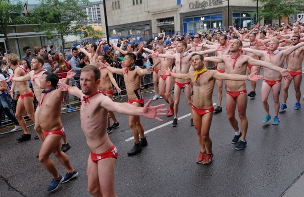 trigger fish waterpolo team parades in their red swim suits, dancing to music, arms out at their sides, passing in front of College Park building