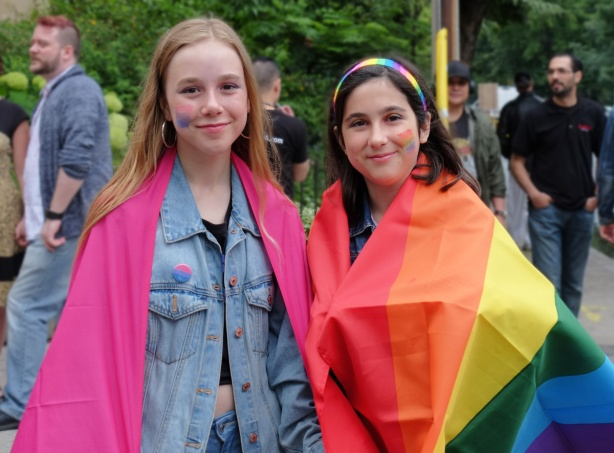 watching the dyke march 2018 - two girls on Yonge street draped in rainbow flags