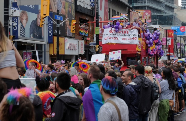 the United Church of Canada float in the Pride Parade, people lining the sidewalks on both sides of the street, people walking in front of the float