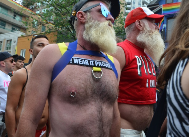 two men with big beards. one in a short red top and red cap, the other topless except for shoulders straps