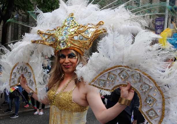 drag queen in elaborate gold costume with white feathers on fans one in each hand) and headdress that also has a large gold glittery star shape front piece