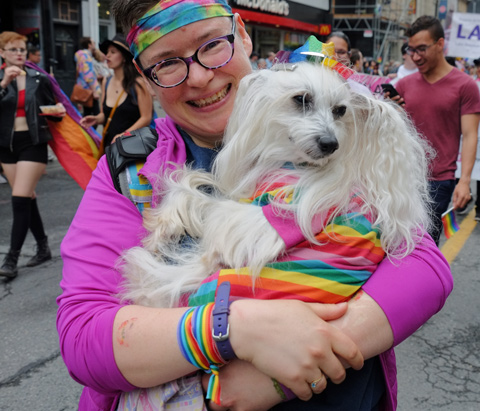 dyke march 2018 - a woman with rainbow headband and pink top is holding a small fluffy white dog with rainbow hat and coat