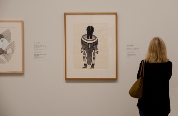 woman in an art gallery looking at two pictures on the wall, both by Kenojuak Ashevak