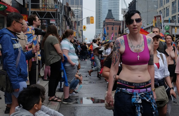dyke march 2018 - woman in pink bra with many tattoos is walking past a crowd on the sidewalk