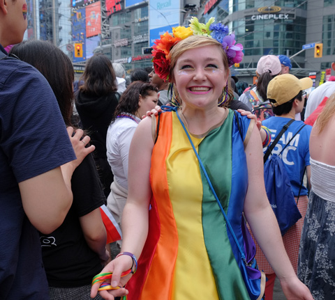 a woman wearing a rainbow dress and garland in her hair, smiling
