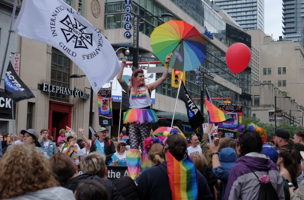 a woman on stilts carries a rainbow umbrella as she walks with iatse group in the pride parade