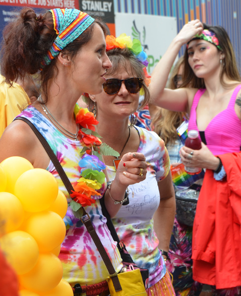 two women talking, with rainbow headbands and colourful clothes, as another woman walks past behind them