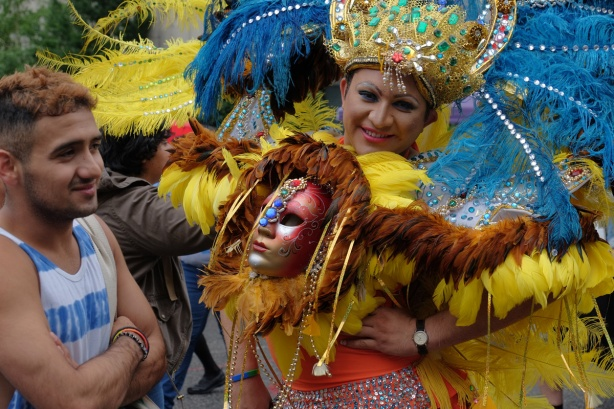 man in drag - blue and yellow feathers, lots of sequins and glitter, carrying a mask