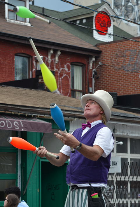 a man wearing a purple vest and white hat, stands on stilts with long trousers covering, juggling 4 different coloured bats (or pins?) shaped a bit like bowling pins, two in his hands and two in the air.  outside on the street