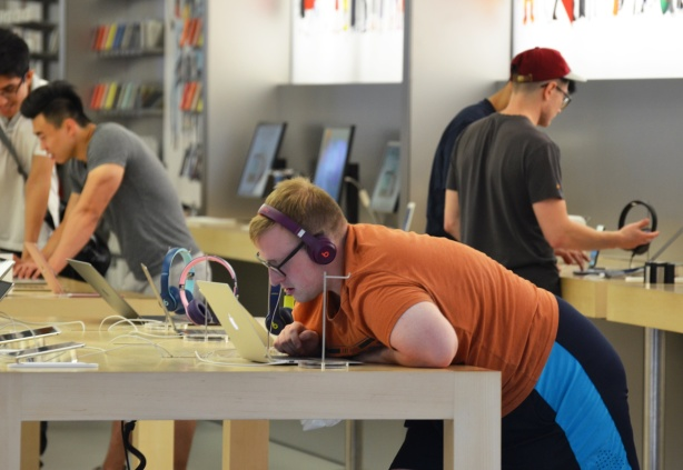 man in an apple store, orange T-shirt, leaning on the counter, with headphones on, looking closely at the screen of a laptop, other men in the store too