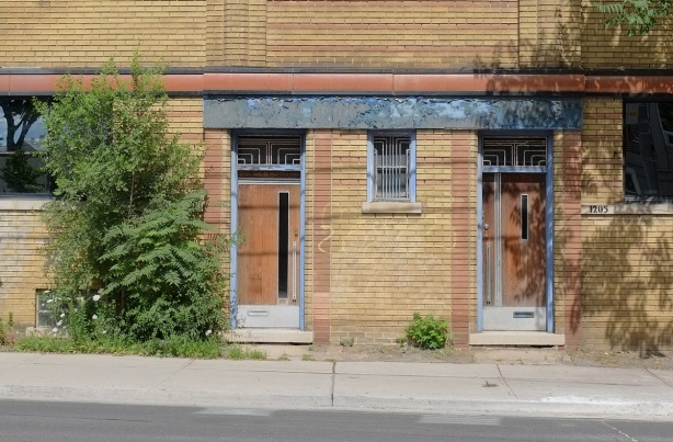 two doors side by side with art deco motifs, on a low rise brick building