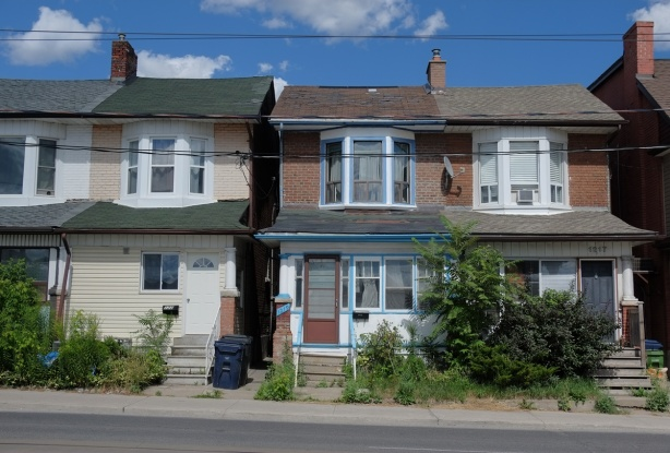 a semi divided house on bathurst street, two storey, bay windows on upper floor, porches, stairs to front door