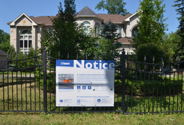 a city of Toronto blue and white notice of development sign is on a black wrought iron fence in front of a large stone faced two storey house with a large front yard, grass and shrubs