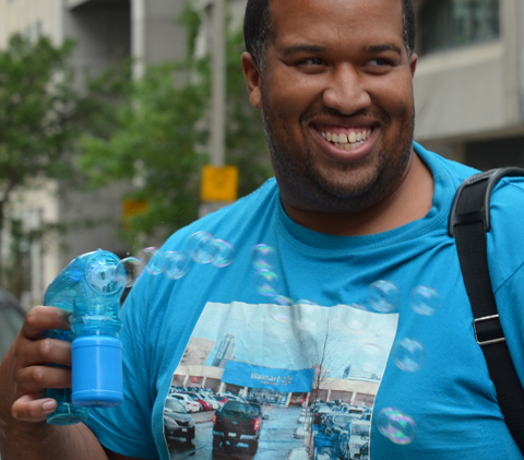 black man with blue t-shirt holds a blue bubble maker and he is making bubbles as he walks down the street