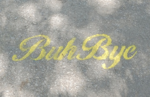yellow stencil on a sidewalk, in cursive writing, buh bye