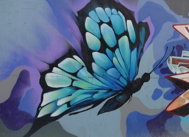 spray paint street art mural of a blue and black butterfly