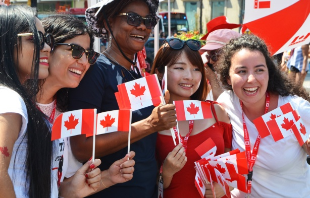a group of women pose with little Canadian flags, for a picture, at Yonge Dundas Square for Canada Day.