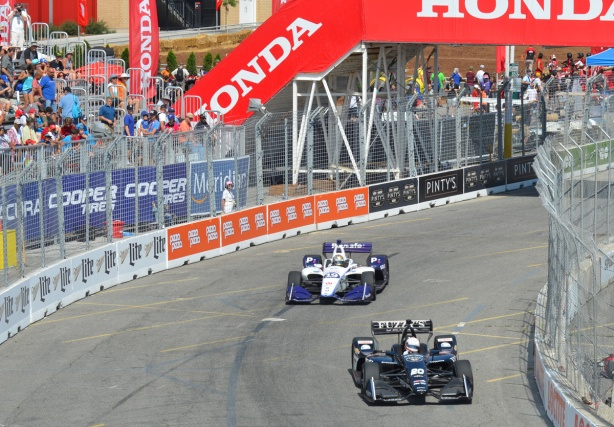 two race cars pass by stands at Honda Indy