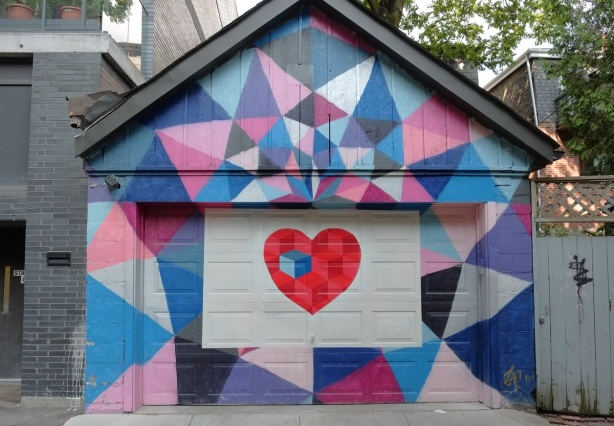 garage and garage door painted in mural with a red heart in the center, surrounded by pink, purple and blue triangles