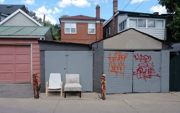 two comfy chairs in an alley withtheir backs agains a grey garage door