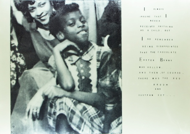 old black and white photo of a black girl, smiling, in dress, with words beside that say ""