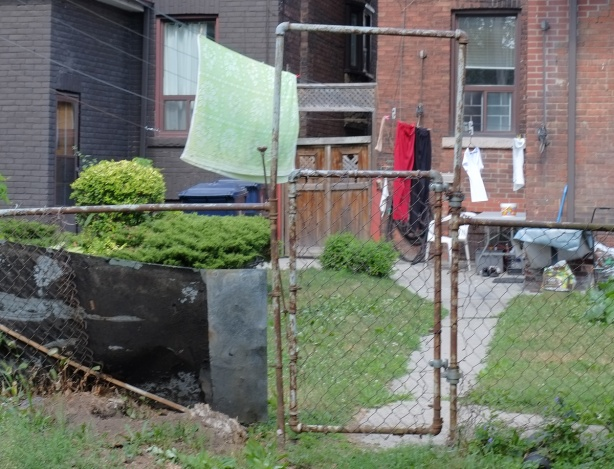 a chainlink fence and gate in a back yard, laundry hanging out to dry in the yard, brick houses, some green grass