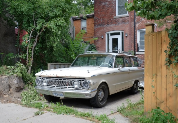 a yellowish beige Comet car, old, parked behind a house in a lane
