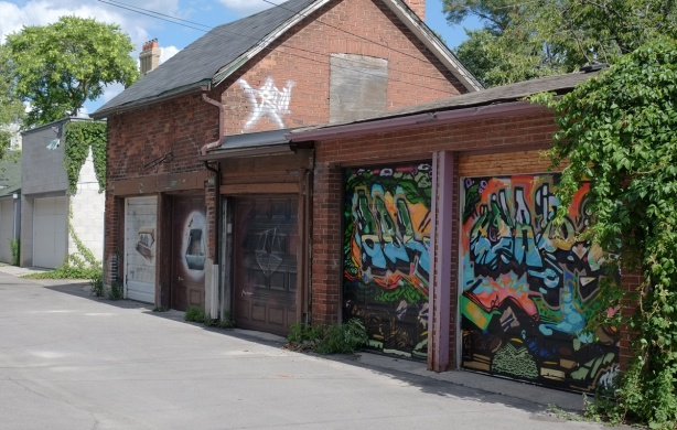 buildings and garages in a lane, Coopers Hawk Lane, garage doors have street art on them.
