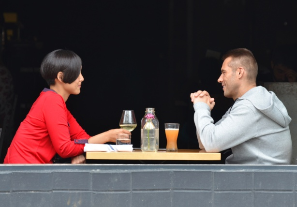a couple sitting in a restaurant, across from each other, in the window, window is open, drinks on the table .  Woman has glass of white wine, man has something orange