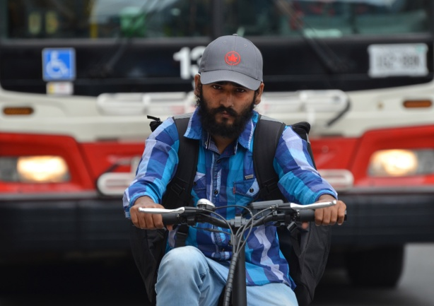 man with beard and moustache, one a bike that is stopped in front of a red and white TTC bus, man wearing a blue baseball cap with red Air Canada maple leaf logo on it
