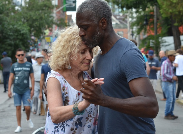 a black man dances on the street, slow dance, with an older blond woman,