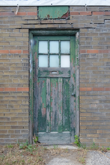 old wood door, once painted green but the paint is peeling