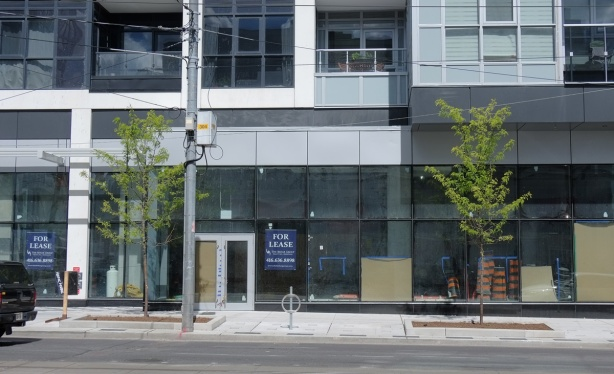 street level of a new glass and steel building, empty retail space available for lease, just finishing being built