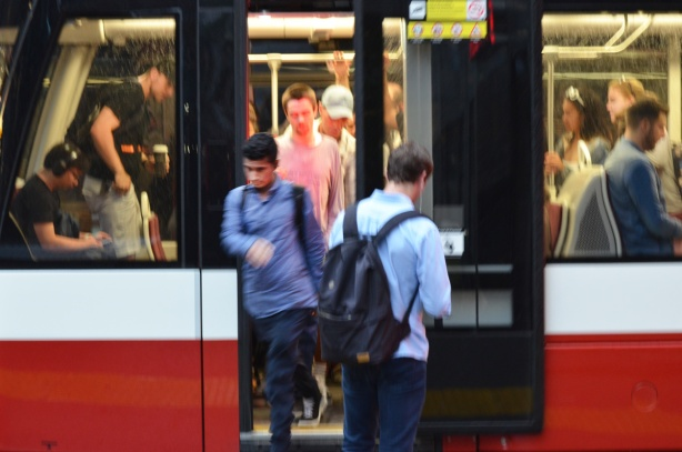 people in the midst of getting on and off a streetcar