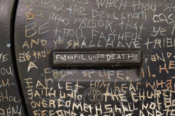 words from Revelations in the New Testament of the bible scratched into paint covering the whole surface of a trans am car, close up of door handle with the words faithful until death on it,