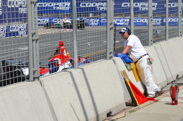 flag man watches the race at Honda Indy, flags beside him as well as fire extinguishers