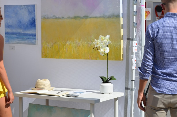 two paintings in a booth at an outdoor art fair, one is yellow, there is a table in front of it, with a flower and and a hat on it, a man walks past