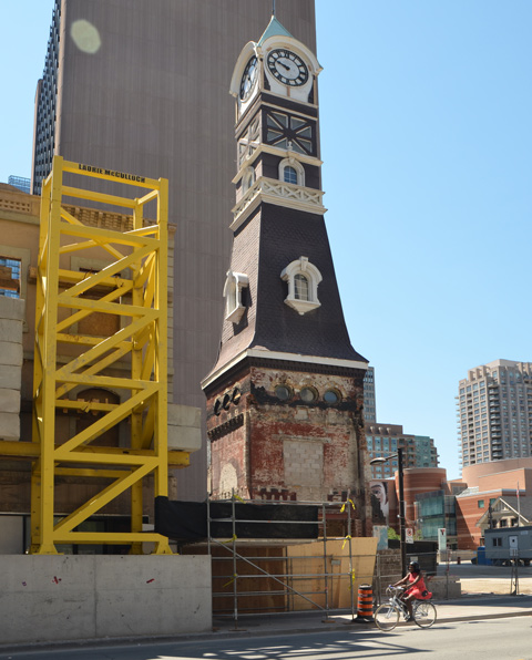 St. Charles tavern clock tower stands on a construction site as a woman on a bike cycles past