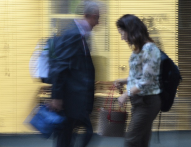 two people, slightly out of focus pass by a lit window