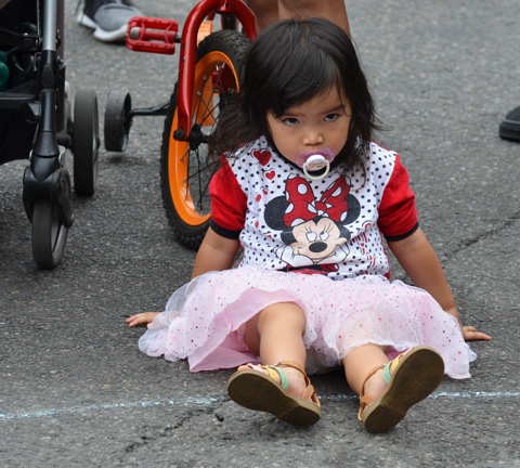 young girl in Minnie Mouse tshirt and frilly pink skirt, pacifier in mouth, sits on the street beside a bike while she watched a performer, summer afternoon,