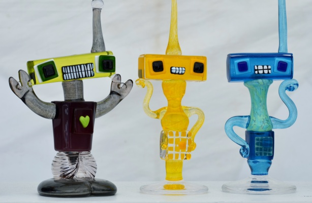 three little glass sculptures of little robot like creatures with rectangular heads and one large antenna