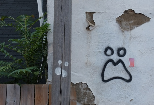 graffiti on wall and on wood pole, both are faces with mouth and two round eyes