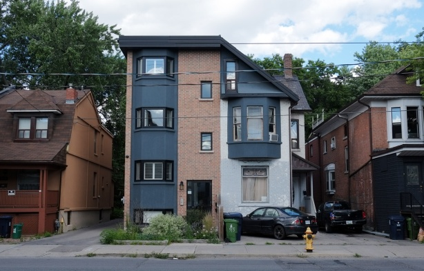 a semi divided house on bathurst street where one side has been rebuilt into a taller square structure